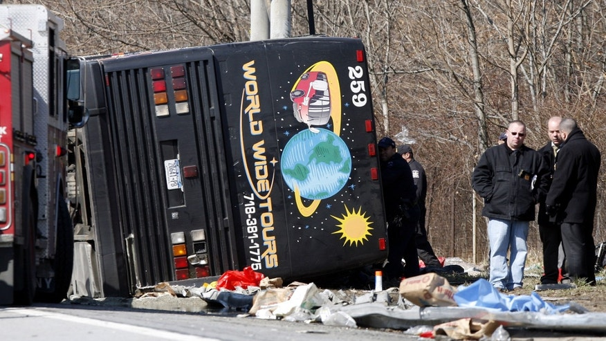 In this photo from Saturday, March 12, 2011, emergency personnel investigate the scene of a bus crash on Interstate-95 in the Bronx borough of New York.