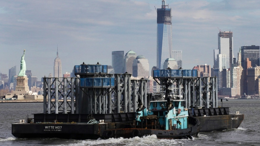 Dec. 11, 2012: A barge loaded with sections of spire for One World Trade Center, center, is guided by tugboat across New York Harbor. The Statue of Liberty is at left, and the Empire State Building is second left.