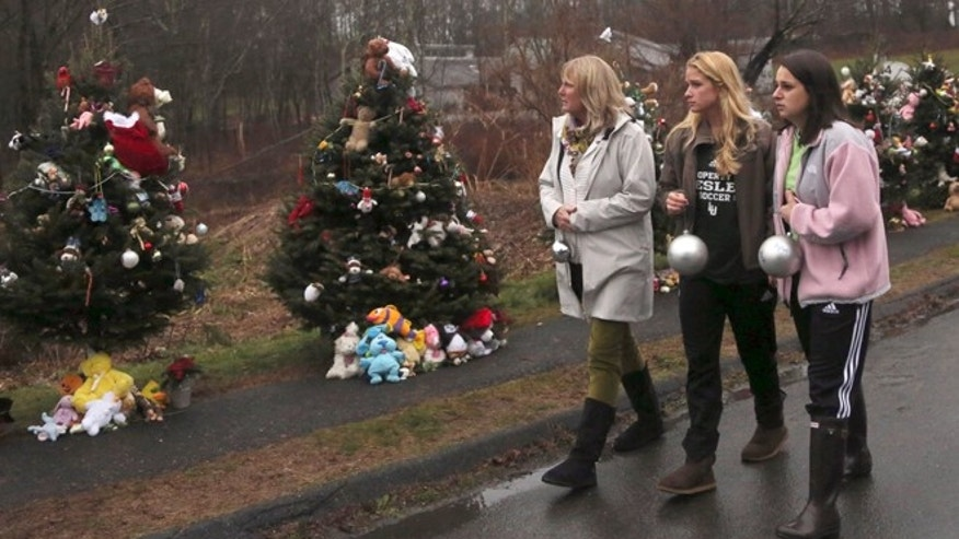 Dec. 17, 2012: Mourners carry ornaments to decorate the Christmas trees at one of the makeshift memorials for the Sandy Hook Elementary School shooting victims, in Newtown, Conn.