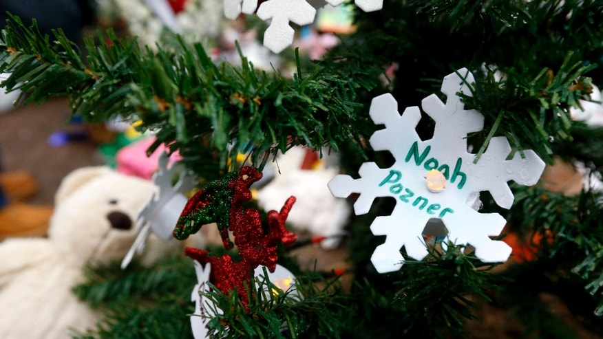 Dec. 17, 2012 - A snowflake ornament with the name of 6-year-old Noah Pozner hangs on a Christmas tree at a makeshift memorial in the Sandy Hook village of Newtown, Connecticut.