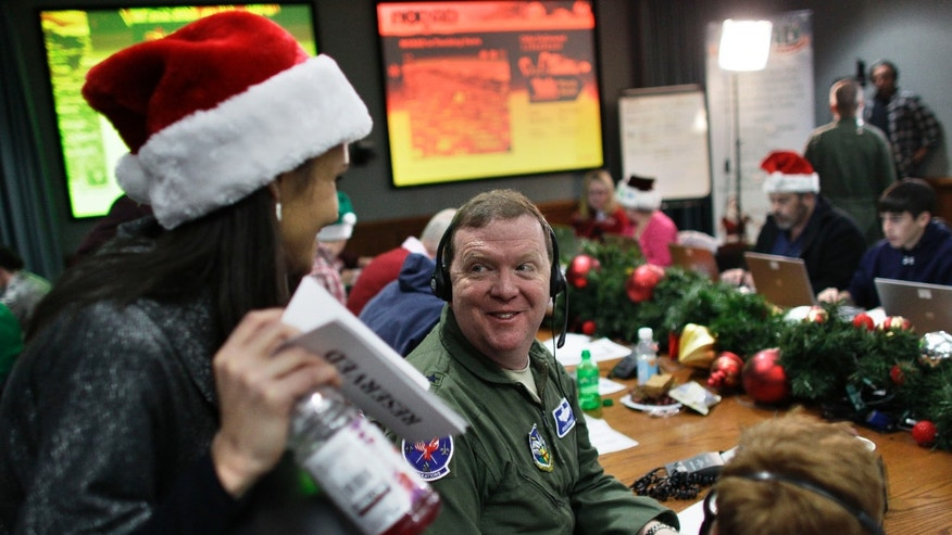 U.S. Air Force Brig. Gen. Richard Scobie talks with a fellow volunteer while taking phone calls from children asking where Santa is and when he will deliver presents to their house, during the annual NORAD Tracks Santa Operation, at the North American Aerospace Defense Command, or NORAD, at Peterson Air Force Base, in Colorado Springs, Colo., Monday Dec. 24, 2012. Over a thousand volunteers at NORAD handle more than 100,000 thousand phone calls from children around the world every Christmas Eve, with NORAD continually projecting Santa's supposed progress delivering presents. (AP Photo/Brennan Linsley)