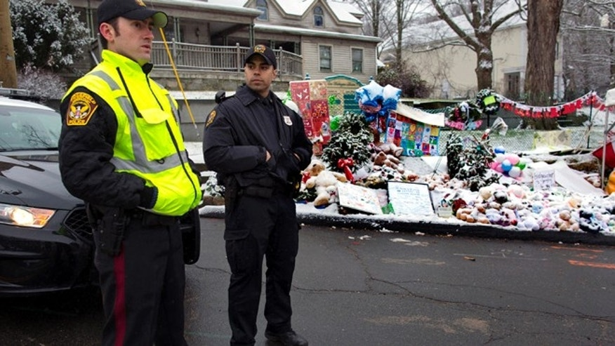 Dec. 25, 2012: From left, Town of Ridgefield, Conn., Det. Durling, and Town of Greenwich, Conn., Officer Rivera stand near a memorial in Newtown, Conn.