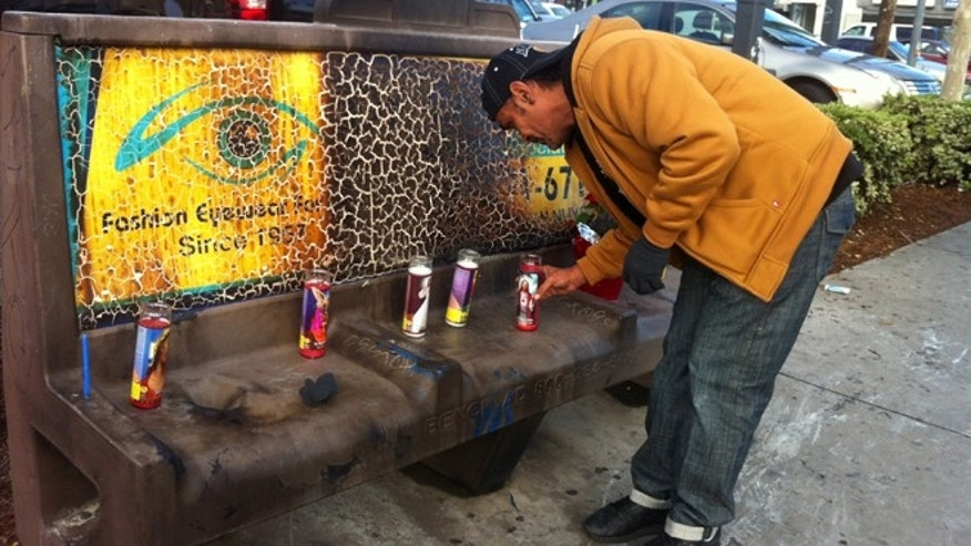 Dec. 27, 2012: Phil Furtado places candles on a burned city bus bench in Los Angeles.
