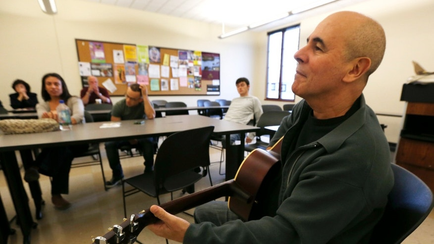 In this Oct. 10, 2012, photo, musician Julio Fernandez holds a guitar during a class session at Montclair State University in Montclair, N.J. Students are participating in a music class for service men and women that helps them cope with their life after the military through a program called Voices of Valor. (AP Photo/Julio Cortez)
