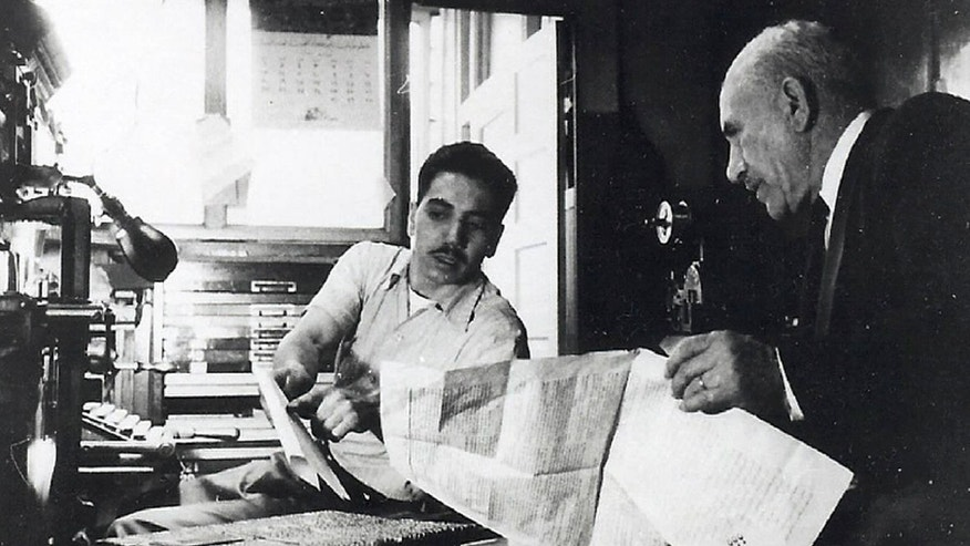 In this early 1950s photo, Hussien Karoub, right, talks with his son Muhammad Karoub at his Karoub Printing business in Highland Park, Mich. (AP Photo/Karoub Family)