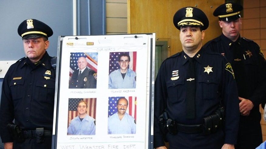 Dec. 25, 2012: Monroe County Sheriff Deputy Chief Steve Scott, second from right, and Webster Police Lt. Joseph Rieger stand by the photo of the dead and injured firefighters during a news conference in Webster, N.Y.