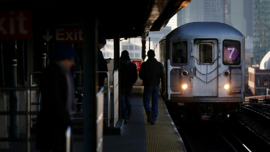 Dec. 28, 2012: Commuters  walk on the platform as a train enters the 40th St-Lowry St Station, where a man was killed after being pushed onto the subway tracks, in the Queens section of New York.