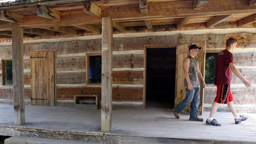 June 9, 2012: Jordan Stamper, right, and James Ball look over a cabin that marks the site of key events in the Hatfield-McCoy feud.