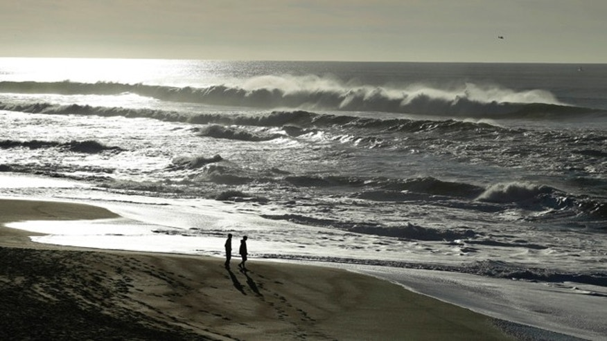 Jan. 1: A couple walk along the North Beach as a helicopter searches for a man lost in the high surf at the Point Reyes National Seashore.