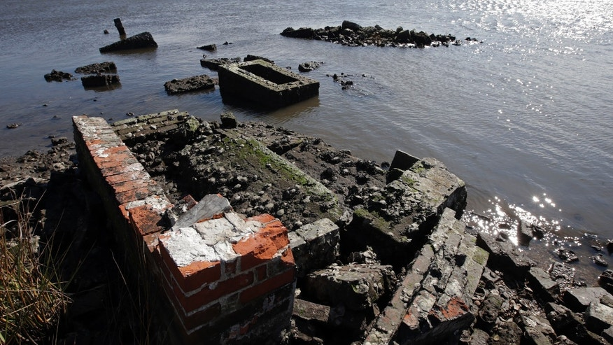 In this Dec. 29, 2012 photo, water washes around and against the tombs of those buried in a Leeville, La., cemetery. What's left of the old Leeville cemetery is only accessible by boat. Some headstones are barely visible above the water, and waves lap at the bricks and concrete surrounding caskets buried at the site since the late 1800s. Much of the ground has subsided to barely sea level, and during Hurricane Isaac, about seven feet of land washed away in the tidal surge. (AP Photo/Dave Martin)