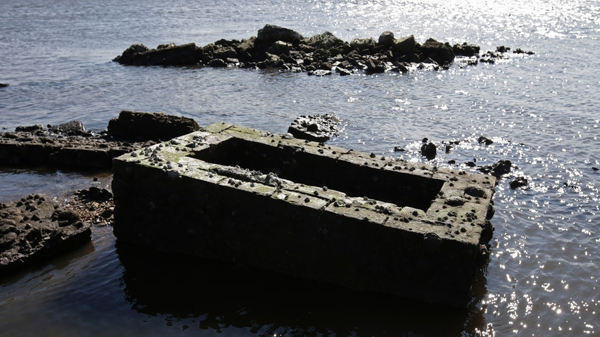 In this Dec. 29, 2012 photo, water washes around an infant's tomb in a Leeville, La., cemetery. What's left of the old Leeville cemetery is only accessible by boat. Some headstones are barely visible above the water, and waves lap at the bricks and concrete surrounding caskets buried at the site since the late 1800s. Much of the ground has subsided to barely sea level, and during Hurricane Isaac, about seven feet of land washed away in the tidal surge. (AP Photo/Dave Martin)