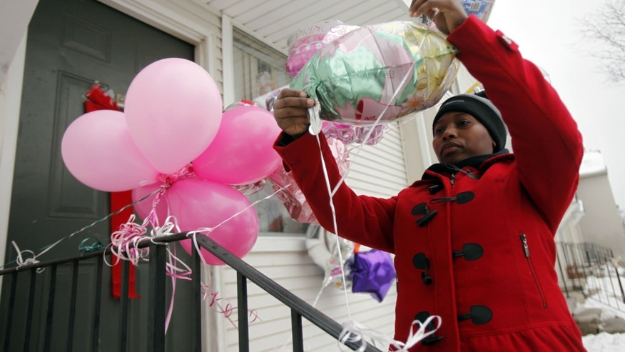 In this photo taken Monday, Dec. 31, 2012, Dornecia Helms, of Detroit places up balloons on the door step of an eight year-old stabbing victim Tameria Greene at the Martin Luther King Apartments, in Detroit. Semeria Greene was charged Wednesday with felony murder in the stabbing death of her daughter Tameria Greene, at their Detroit home just days before the girl's 9th birthday. (AP Photo/Detroit Free Press, Andre J. Jackson)  DETROIT NEWS OUT&#x3b; NO SALES&#x3b; INTERNET OUT&#x3b; MAGS OUT&#x3b; TV OUT&#x3b; MANDATORY CREDIT