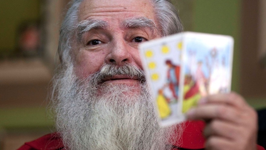 "Antonio Vazquez Alba, popularly known as the ""Grand Warlock,"" holds up Tarot cards as he gives his traditional predictions for the new year during a press conference in Mexico City, Friday, Jan. 4, 2013. After reading some of his dozens of predictions, Vazquez took questions from reporters and said tarot cards showed Venezuelan President Hugo Chavez, who is battling cancer, will make it to his inauguration but that he will be dead by April. (AP Photo/Eduardo Verdugo)"