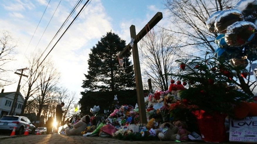 A man visiting from Michigan takes photos of a makeshift memorial near the town Christmas tree in the Sandy Hook village of Newtown, Conn., Wednesday, Dec. 19, 2012. The memorial, which was put up in the aftermath of the elementary school shooting that shocked the small town, is increasing in size as the days go on. More funerals are scheduled for Wednesday, as the town continues to mourn its victims. The gunman, Adam Lanza, walked into Sandy Hook Elementary School in Newtown, Conn., Dec. 14, and opened fire, killing 26 people, including 20 children, before killing himself. (AP Photo/Julio Cortez)