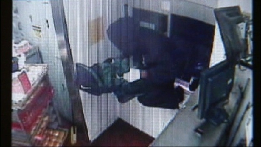 This screen shot of surveillance video shows a suspect jumping through a McDonald's drive-thru window.