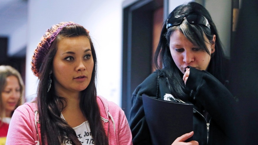 Chantel Blunk, left, leaves with a family member following a preliminary hearing for James Holmes at the courthouse in Centennial, Colo., on Monday, Jan. 7, 2013. Investigators say Holmes opened fire during the midnight showing of the latest Batman movie on July 20, killing 12 people and wounding dozens. Blunk's husband Jon was killed in the shooting. (AP Photo/Ed Andrieski)