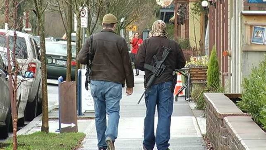 This image, obtained by Fox affiliate KPTV, shows two men walking through Portland Wednesday with assault rifles. The men reportedly told officers that they were hoping to educate the public on gun rights.