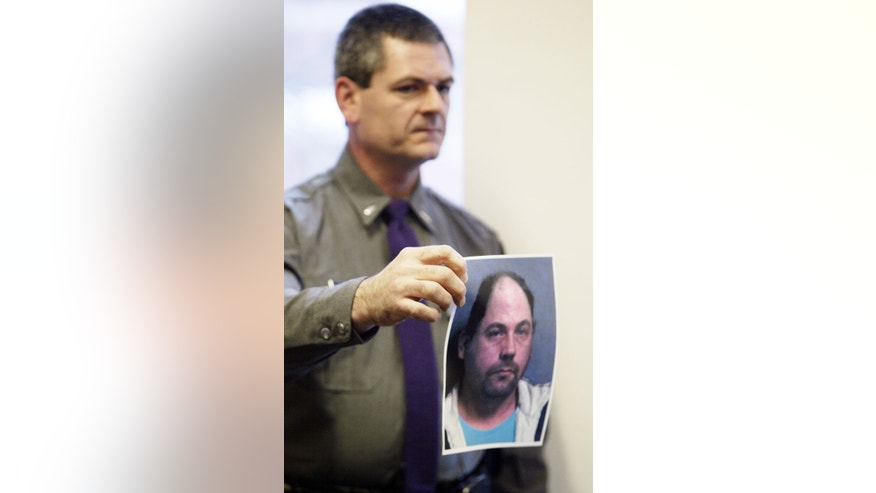 In this Jan. 2, 2013 photo, New York State Police Lt. John Durling shows a picture of 39-year-old serial burglary suspect John W. Suddard, Jr. during a news conference at Hudson Falls Village Court in Hudson Falls, N.Y. Few clues exist pointing to the owners of the roughly 30,000 items discovered after Suddard's recent arrest. So police are taking the novel step of displaying the items at the local high school Wednesday night, Jan. 9, 2013. (AP Photo/The Post-Star, Derek Pruitt)