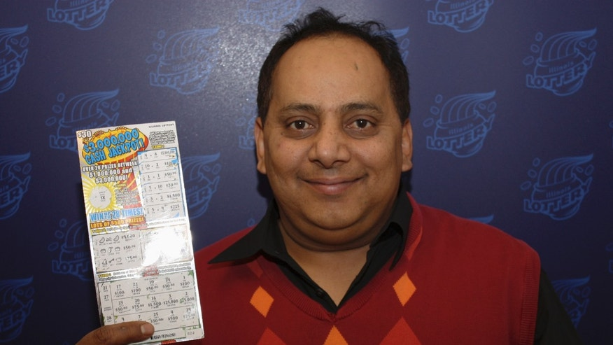 FILE - This undated file photo provided by the Illinois Lottery shows Urooj Khan, 46, of Chicago's West Rogers Park neighborhood, posing with a winning instant lottery ticket.