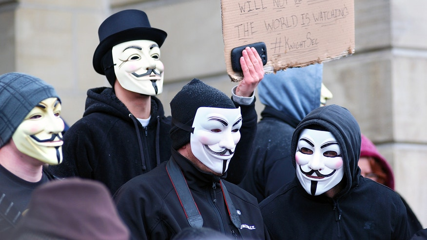 Members of the group Anonymous, wearing Guy Fawkes masks, protest alleged cover-up in the case of two eastern Ohio high school football players charged with raping a 16-year-old girl. (AP Photo/Herald-Star, Michael D. McElwain)