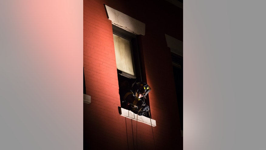 A firefighter feeds a cable out of a burned window of 41 Spring Street in lower Manhattan after it was engulfed in a five alarm fire that had been contained, Thursday, Jan. 10, 2013, in New York. One person has died and eight people were injured. (AP Photo/John Minchillo)