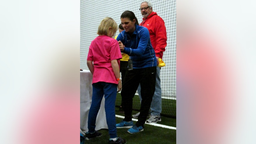 FILE - In this Monday, Jan. 7, 2013 file photo, retired soccer player Mia Hamm, center, signs an autograph during a visit by MLS and United States national team players to the Newtown Youth Academy in Newtown, Conn. The event, which was set up by Houston Dynamo general manager and Connecticut native Chris Canetti, featured about 40 current and former soccer players interacting with and signing autographs for about 1,000 children in a community that was devastated by the deadly shooting at the Sandy Hook Elementary School. (AP Photo/Pat Eaton-Robb, File)