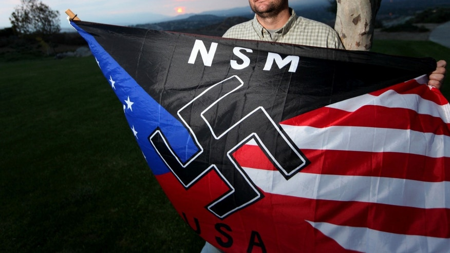 FILE - In this Oct. 22, 2010 file photo, Jeff Hall, who was killed by his son, holds a Neo Nazi flag while standing at Sycamore Highlands Park near his home in Riverside, Calif. Defense attorneys for a boy charged with killing Hall, his neo-Nazi father when he was 10 years old has rested its case without calling the boy to testify, Wednesday, Jan. 9, 2013. (AP Photo/Sandy Huffaker, File)