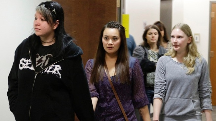 Jan. 11, 2013: Chantel Blunk, center, holds hands with two women as they arrive for a court proceeding for Aurora theater shooting suspect James Holmes at the courthouse in Centennial, Colo.