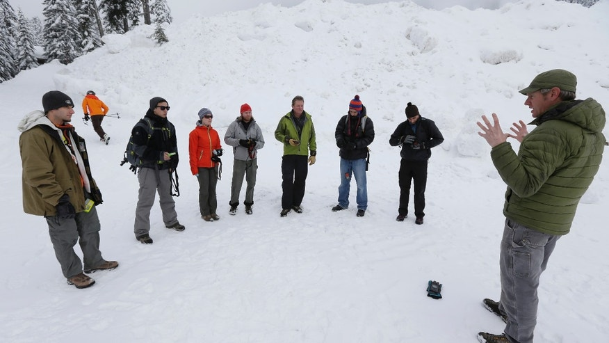 In this Jan. 4, 2013 photo, instructor Dave Jordan, right, teaches an avalanche safety course on Snoqualmie Pass in Washington state. Where backcountry safety education once stressed the mechanics of avalanches and snow science, training courses now incorporate a focus on human factors such as how to make better decisions, manage group dynamics and speak up should danger arise. (AP Photo/Ted S. Warren)