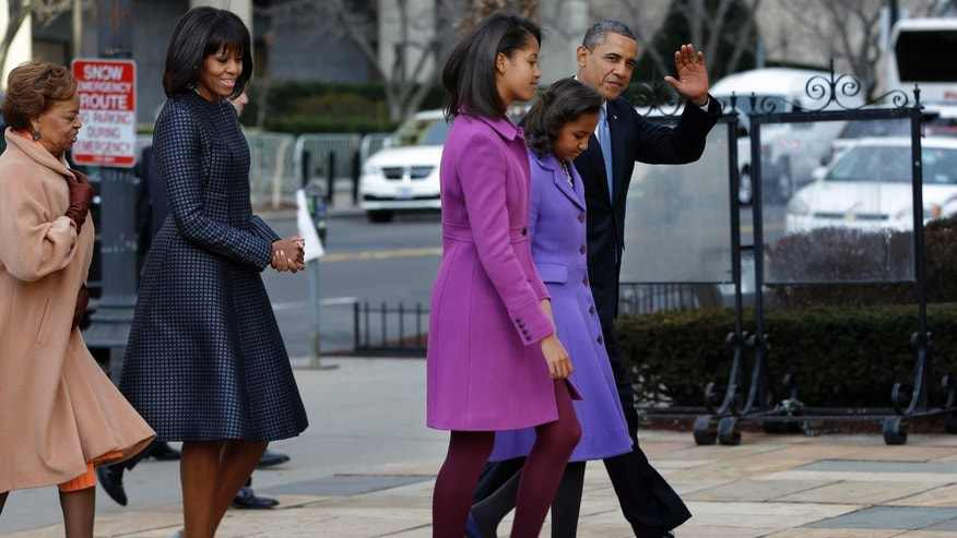 President Barack Obama, accompanied by his daughters Sasha and Malia, first lady Michelle Obama and mother-in-law Marian Robinson, waves as they arrive at St. John's Church in Washington, Monday, Jan. 21, 2013, for a church service during the 57th Presidential Inauguration. (AP Photo/Jacquelyn Martin)
