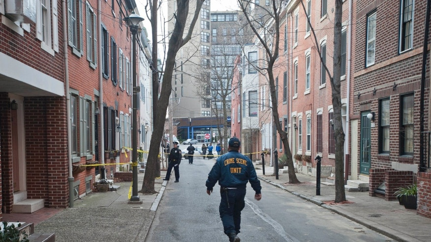 A Philadelphia Police crime scene unit officer walks down the 1700 block of Naudain St. in Center City where a woman was found burned to death in her basement, Monday, Jan. 21, 2013 in Philadelphia. Philadelphia police Chief Inspector Scott Small says firefighters responding to the home Monday afternoon found the woman's body on fire, with her ankles and wrists bound. Officer Christine O'Brien, a police department spokeswoman, said Tuesday the victim has been identified as 35-year-old Melissa Ketunuti. O'Brien says the cause of death has not been determined. An autopsy is scheduled for Tuesday. (AP Photo/Philadelphia Inquirer, Ron Tarver)  MAGS OUT; NEWARK OUT