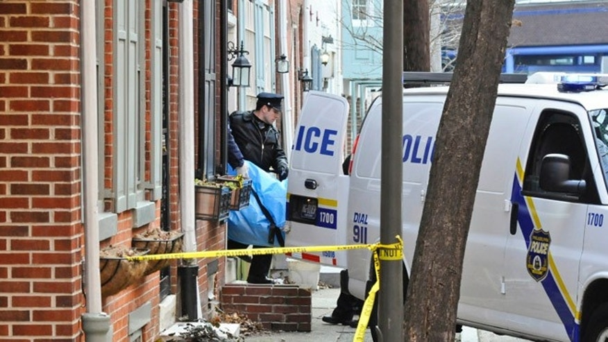 Jan. 21, 2013: Police remove the body of a woman found burned to death in her basement on the 1700 block of Naudain St. in Center City in Philadelphia.