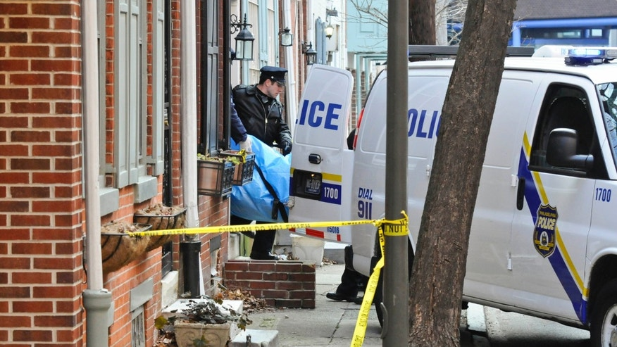 Police remove the body of a woman found burned to death in her basement on the 1700 block of Naudain St. in Center City Monday, Jan. 21, 2013 in Philadelphia. Philadelphia police Chief Inspector Scott Small says firefighters responding to the home Monday afternoon found the woman's body on fire, with her ankles and wrists bound. Officer Christine O'Brien, a police department spokeswoman, said Tuesday the victim has been identified as 35-year-old Melissa Ketunuti. O'Brien says the cause of death has not been determined. An autopsy is scheduled for Tuesday. (AP Photo/Philadelphia Inquirer, Ron Tarver)  MAGS OUT; NEWARK OUT