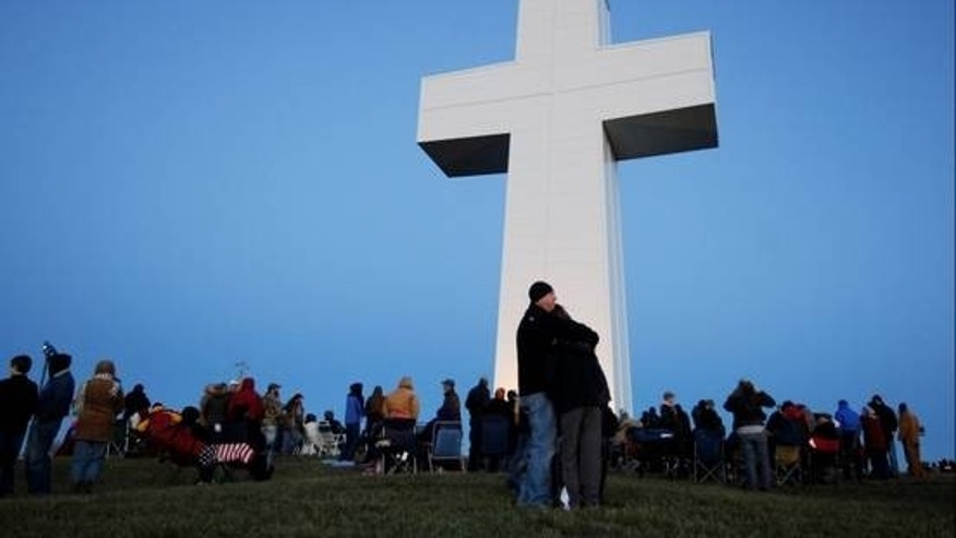 Dec. 22, 2012: Spectators huddle together for warmth before the lighting of the Bald Knob Cross of Peace in Alto Pass, Ill. The lighting ceremony marked the completion of a renovation project that began in 2009. (AP)