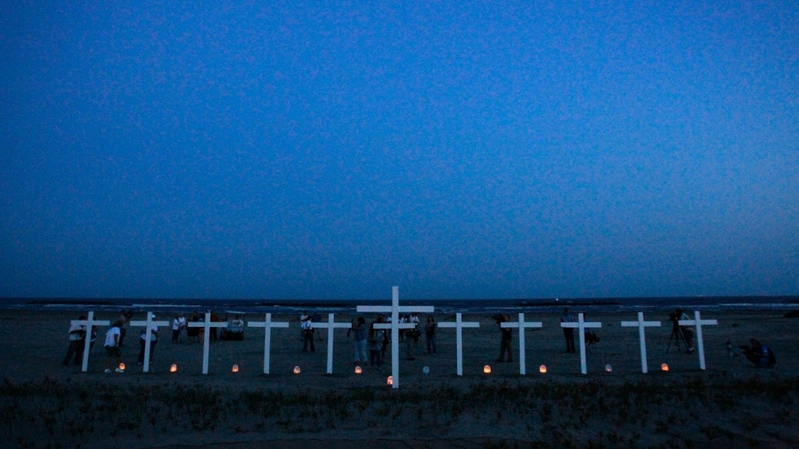 FILE - In a Wednesday, April 20, 2011 file photo, people gather near crosses -11 for the workers who died in the Deepwater Horizon oil rig explosion and one for the Gulf of Mexico, center - during a vigil to mark the first anniversary of the BP PLC oil spill on a beach in Grand Isle, La. A U.S. judge on Tuesday, Jan. 29, 2013, approved an agreement for British oil giant BP PLC to plead guilty to manslaughter and other charges and pay a record $4 billion in criminal penalties for the company's role in the 2010 oil disaster in the Gulf of Mexico. (AP Photo/Patrick Semansky, File)