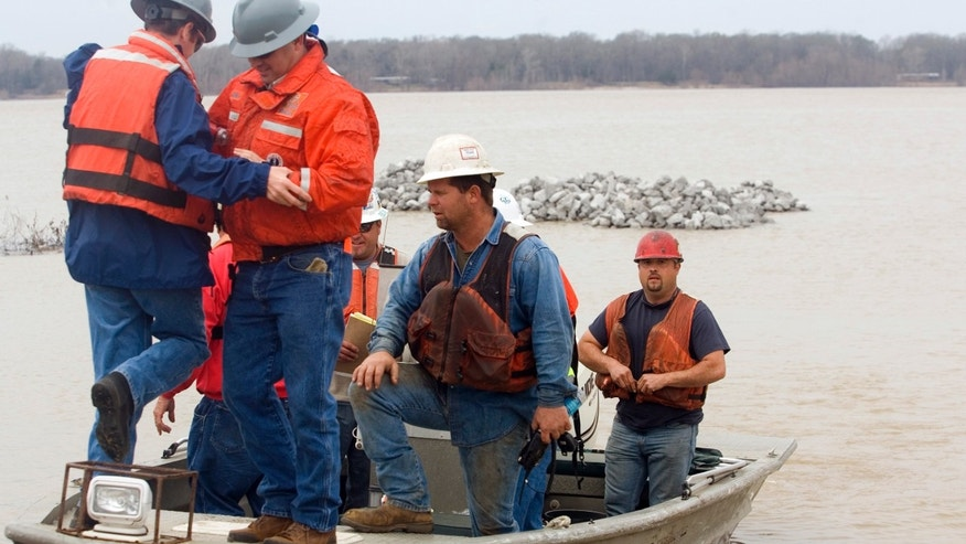 Shannon Warnock, far right, a salvage hand with Big River Ship Builders & Salvage, secures his flotation device after loading a boat with MDEQ employees at Le Tourneau Landing to work on the damaged barge stalled on the west bank of the Mississippi River,  Monday, Jan. 28, 2013 near Vicksburg, Miss.   A barge carrying thousands of gallons of oil struck a railroad bridge and began leaking before dawn Sunday. The accident forced the closure of a 16-mile stretch of the lower Mississippi, a major inland corridor for vessels carrying oil, fuel, grain and other goods. (AP Photo/The Vicksburg Evening Post, Melanie Thortis )  MANDATORY CREDIT