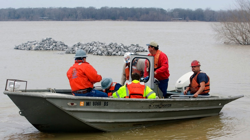Shannon Warnock, far right, salvage hand with Big River Ship Builders & Salvage, leaves Le Tourneau Landing with MDEQ employees to work on the damaged barges stalled on the west bank of the Mississippi River, Monday, Jan. 28, 2013 near Vicksburg, Miss.   A barge carrying thousands of gallons of oil struck a railroad bridge and began leaking before dawn Sunday. The accident forced the closure of a 16-mile stretch of the lower Mississippi, a major inland corridor for vessels carrying oil, fuel, grain and other goods. (AP Photo/The Vicksburg Evening Post, Melanie Thortis )  MANDATORY CREDIT