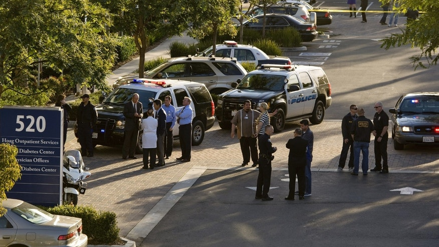 Police and medical personnel stand outside a medical office near Hoag Hospital where shots were fired on Monday, Jan. 28, 2013, in Newport Beach, Calif. Police say a doctor has been shot and killed and a man is in police custody. (AP Photo/The Orange County Register, Leonard Ortiz)