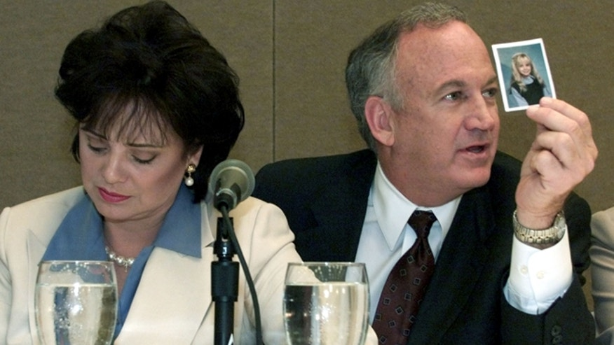 Patsy Ramsey looks down as her husband John Ramsey (R) produces a picture of Jon-Benet Ramsey during a press conference in Atlanta where they released the results of an independant lie detector test on May 24. The Ramsey's appeared with their attorneys and the officials who administered the test stating that they had no knowledge of who killed their daughter Jon-Benet Ramsey in Boulder,Colorado.TLC/RCS - RTR4MMH