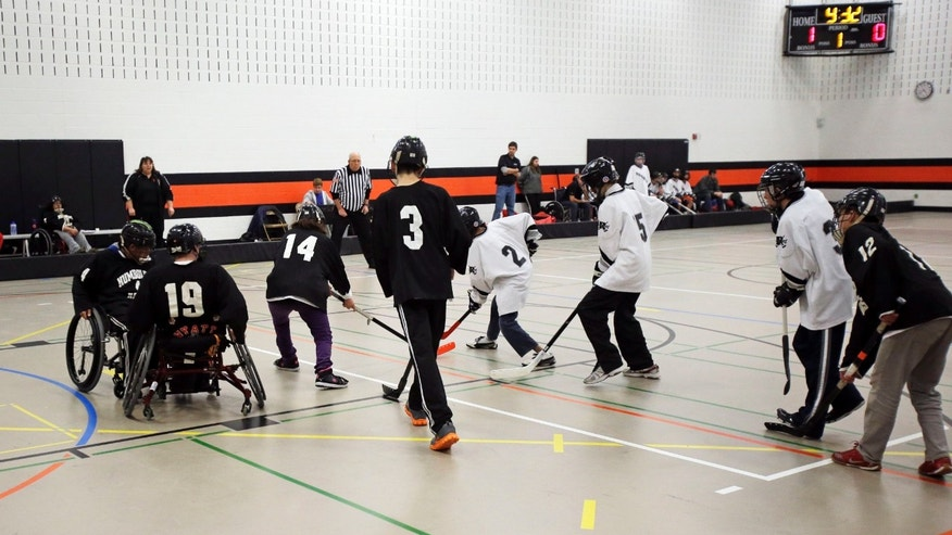 "In this Jan. 29, 2013 photo, high school students participate in a floor hockey game between the home team Humboldt High School Hawk, in black, and the Rochester Raiders in St. Paul, Minn. Floor hockey is one of the ""adapted athletics"" programs the state high school league has run since 1992. Minnesota has become a model state as the federal government pushes schools to include more disabled students in sports. Coaching the Hawks is Mary Bohland, background left. (AP Photo/Jim Mone)"