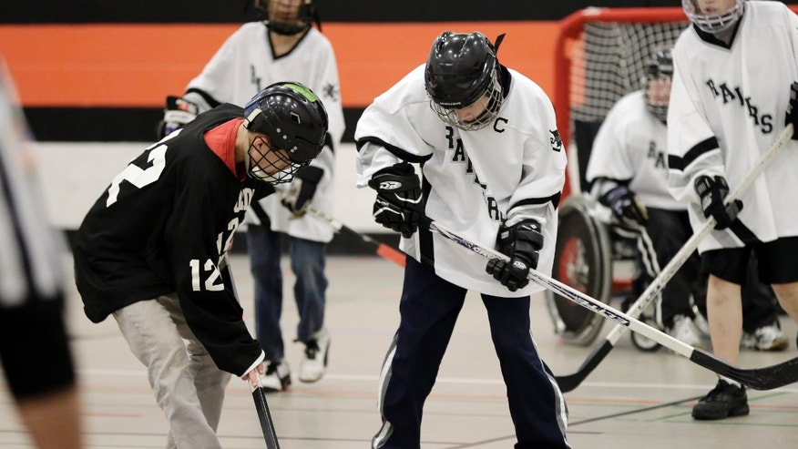 "In this Jan. 29, 2013 photo, high school students participate in a floor hockey game between the Humboldt High School Hawks (in black) and the Rochester Raiders in St. Paul, Minn. Floor hockey is one of the ""adapted athletics"" sports the state high school league has run since 1992. Minnesota has become a model state as the federal government pushes schools to include more disabled students in sports. (AP Photo/Jim Mone)"