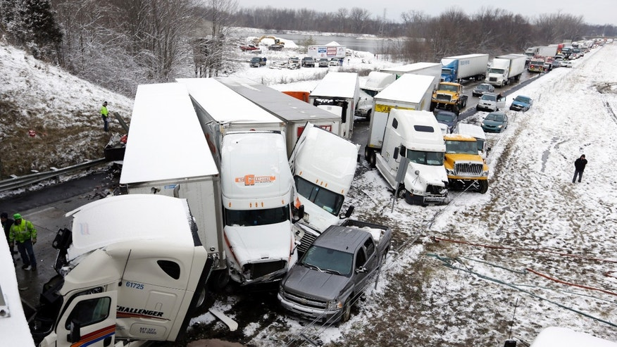 Police and emergency personal work the scene of a pileup involving more than 40-vehicles on Interstate 70 in Plainfield, Ind., Thursday, Jan. 31, 2013. The crash closed the interstate in both direction and authorities reported at least seven minor injuries. (AP Photo/Michael Conroy)