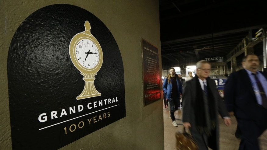 Jan. 9, 2013: Passengers disembarking from a train pass a sign advertising the 100th anniversary of Grand Central Terminal in New York.