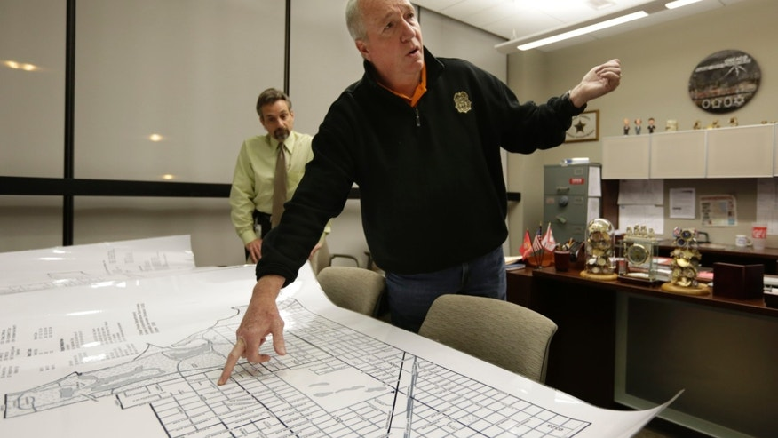 In this Tuesday, Dec. 11, 2012 photo, Jack Riley, center, head of the Drug Enforcement Administration in Chicago, points out local Mexican drug cartel problem areas on a map in the new interagency Strike Force office accompanied by DEA agent Vince Balbo, in Chicago. The first-of-its-kind drug enforcement headquarters has opened in Chicago where 70 federal agents, local police and prosecutors work side-by-side, all year round to fight drug trafficking - a set-up meant to end inter-agency rivalry and miscommunication that can plague investigations. The opening of the Chicago Strike Force office comes as Mexican traffickers have taken control of more than 90 percent of the drugs market in Chicago, which the syndicates also use as a hub for distribution across the Midwest, the DEA says. (AP Photo/M. Spencer Green)