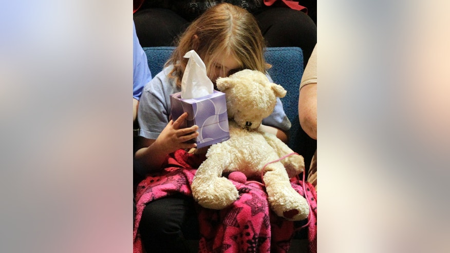 """Lauren Higginson, a student on  Charles """"Chuck"""" Poland's bus, hugs her teddy bear during the ceremony to honor Poland at the Ozark Civic Center on Sunday, Feb. 3, 2013, in Ozark, Ala. (AP Photo/Butch Dill)"""
