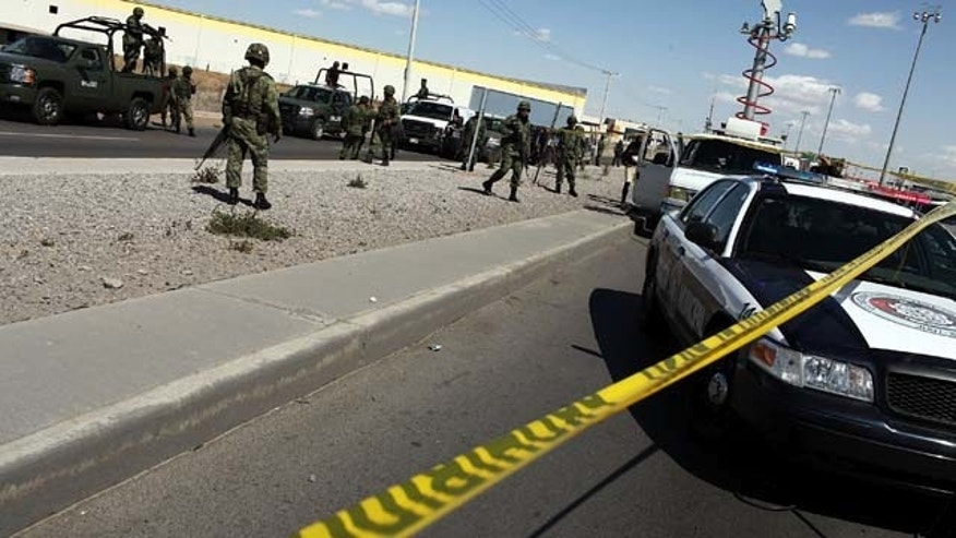 JUAREZ, MEXICO - MARCH 24:  Military police keep guard at the site of a murder on March 24, 2010 in Juarez, Mexico. A Pew Research study found that 61 percent of respondents believe the Mexican and United States' governments were equally to blame for explosion in violence the last few years. (Photo by Spencer Platt/Getty Images)
