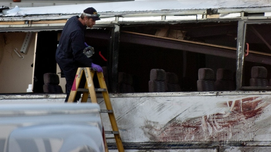 A National Transportation Safety Board official climbs into the bus after a news conference Tuesday, Feb. 5, 2013, at Certified Towing in Ontario, Calif. The NTSB gave an update on the investigation of Sunday's tour bus crash near Yucaipa that killed seven people. (AP Photo/The Inland Valley Daily Bulletin, Jennifer Cappuccio Maher)