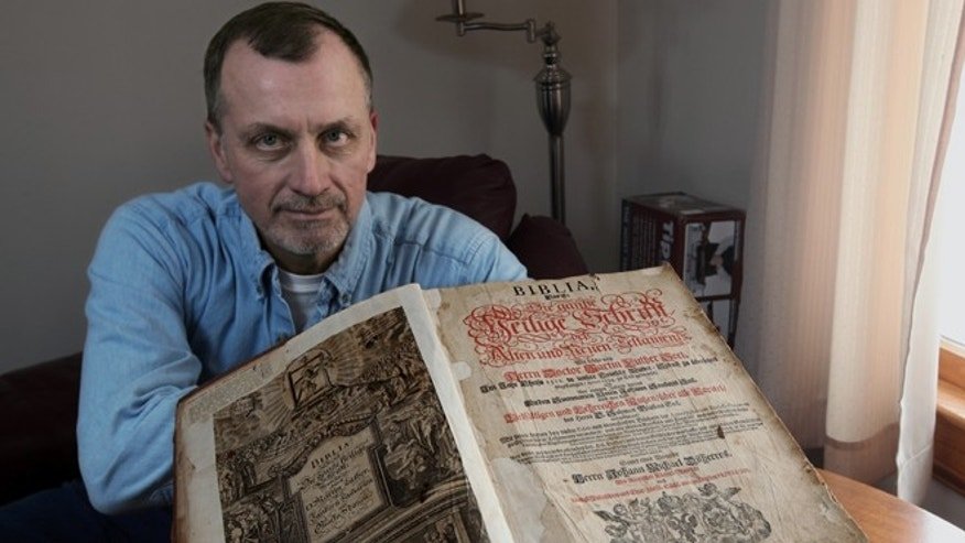 Feb. 3: Tim Shier holds up his family bible dating from the 1700s in his home in Marysville, Ohio.