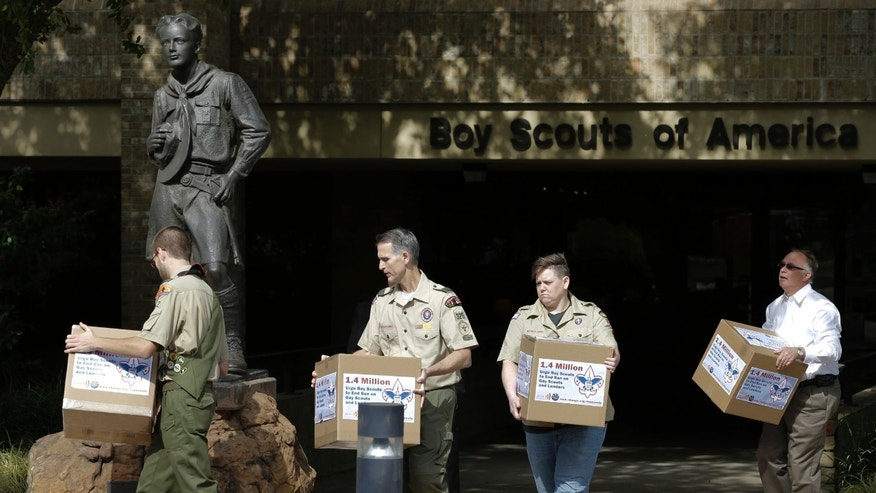 FILE - In this Feb. 4, 2013, photo Eagle Scout Will Oliver, from left, former Scoutmaster Greg Bourke, former den leader Jennifer Tyrrell and Eric Andresen, right, a parent of a gay scout deliver boxes filled with a petition to the statue in front of the Boy Scouts of America headquarters in Irving, Texas. The Boy Scouts of America's policy excluding gay members and leaders could be up for a vote as soon as Wednesday, when the organization's national executive board meets behind closed doors under intense pressure from several sides. (AP Photo/Tony Gutierrez, File)