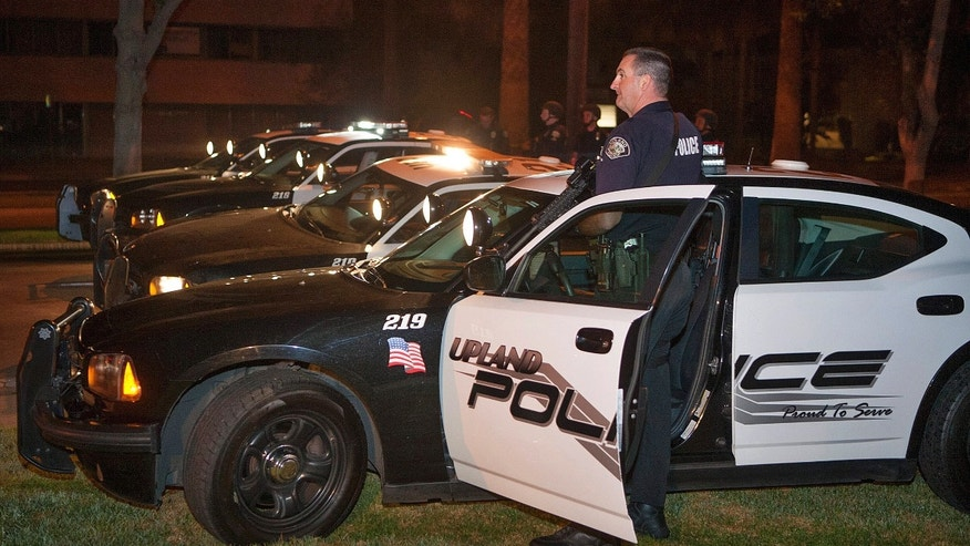 Police respond in Riverside, Calif., early Thursday morning, Feb. 7, 2013, after one officer was killed and another critically wounded in a shoot out with a murder suspect.  Police were searching for a former Los Angeles police officer sought for two weekend killings — and who threatened to kill police.  (AP Photo/Kevin Warn)